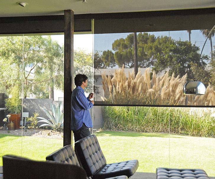 Man enjoying the view outside from the inside of his house