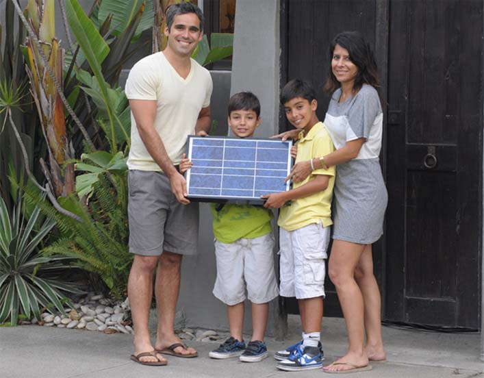 Family holding a solar panel